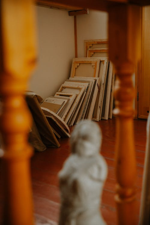 Collection of different size empty frames placed on floor by wall in cozy workshop with blurred sculpture