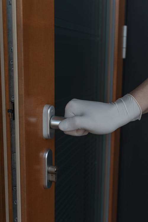 Person Wearing Gloves Holding A Door Knob