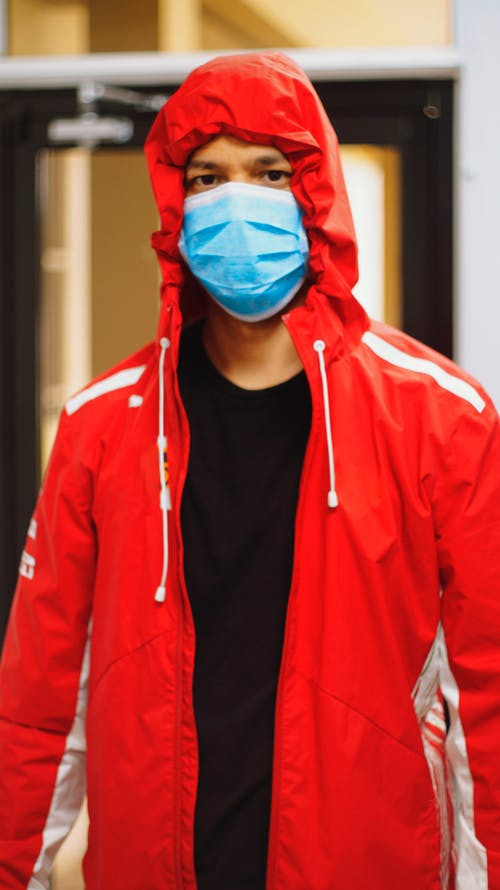 Man in Zip Up Hoodie Wearing Blue Mask
