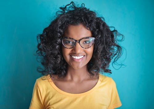 Cheerful black woman in eyeglasses smiling at camera