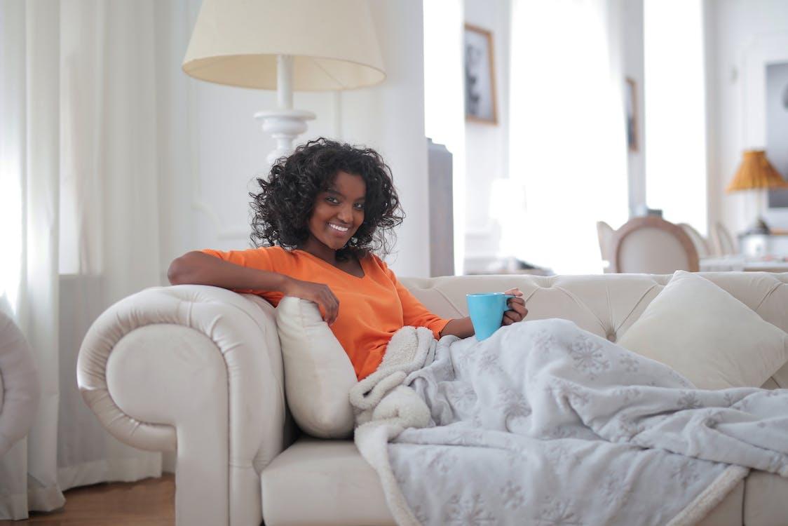 Woman in Orange Long Sleeve Shirt Sitting on White Sofa Chair