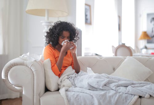 Young black woman covered with blanket blowing nose