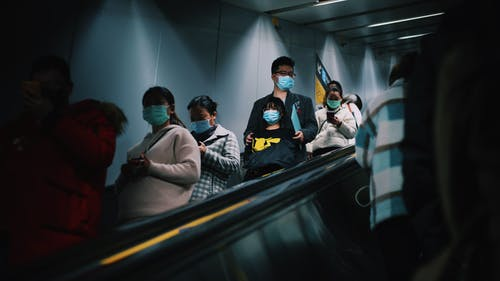 People On A Escalator Wearing Masks