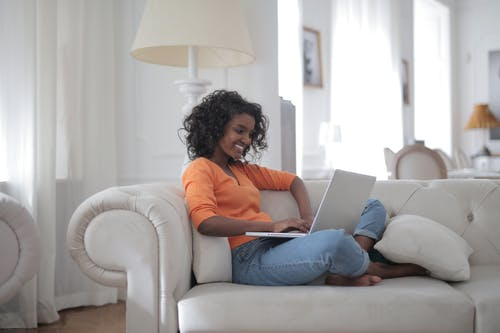 Woman Sitting on White Couch Using Laptop Computer