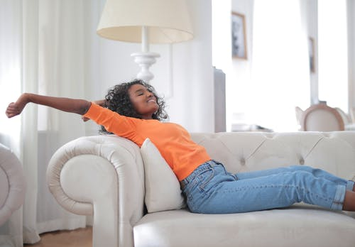 Woman in Orange T-shirt and Blue Denim Jeans Lying on White Sofa