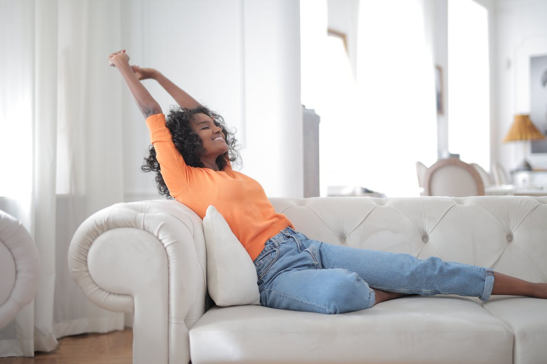 Happy African American female stretching on sofa
