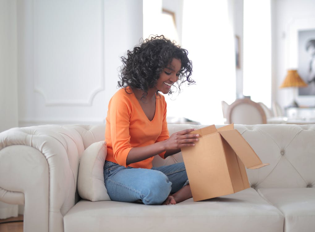 Cheerful African American woman unpacking parcel