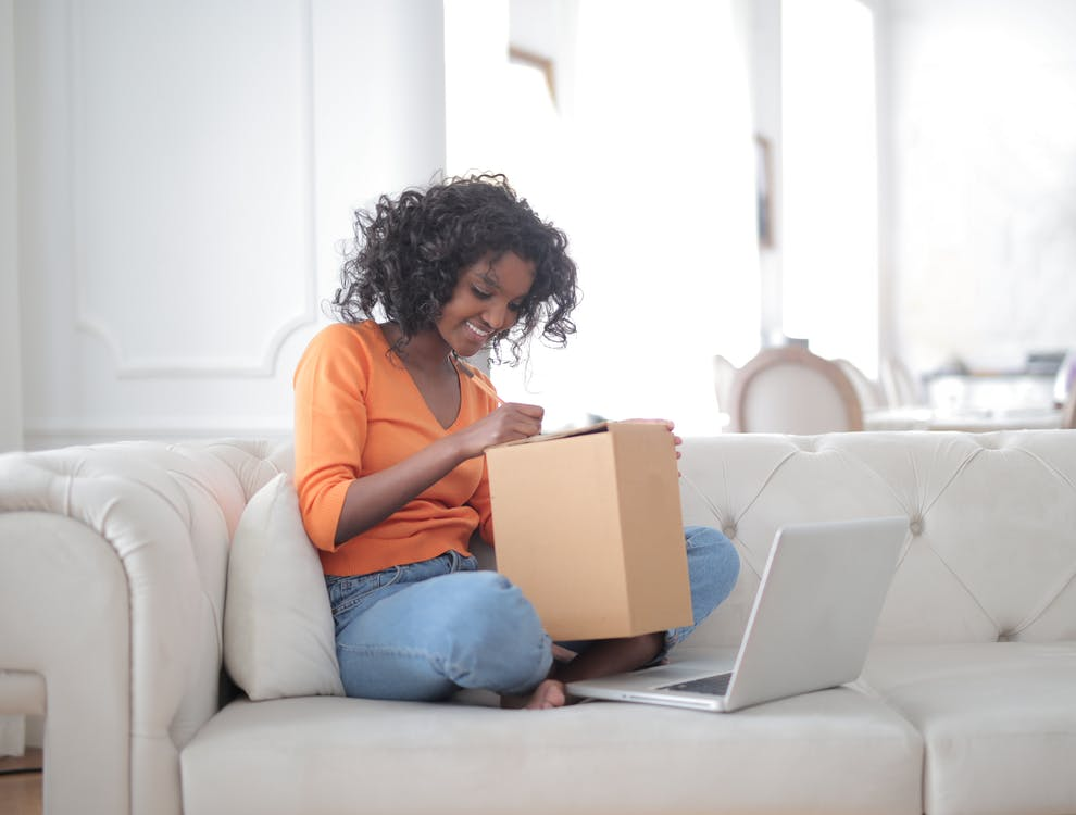 Side view of curly haired cheerful black woman opening carton box while sitting on sofa with laptop