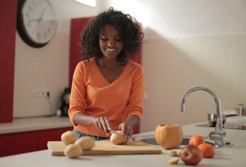 Cheerful woman cutting potatoes in kitchen
