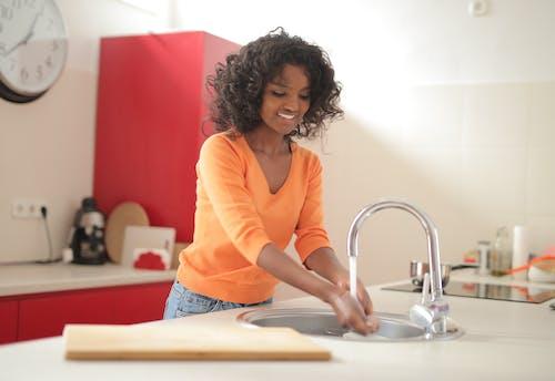 Woman in Orange Long Sleeve Shirt Washing her Hands