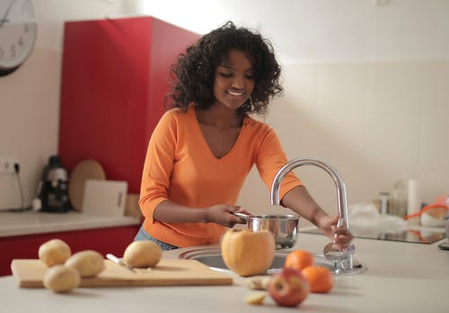 Smiling young ethnic lady in colorful casual clothes standing near sink and pouring water in pot while cooking food in spacious modern kitchen at home