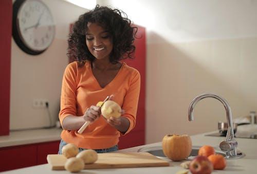 Woman in Orange Long Sleeve Shirt Peeling Potato