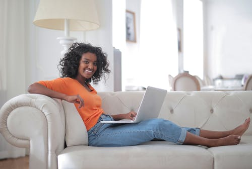 Positive young ethnic lady sitting on sofa with laptop and looking at camera