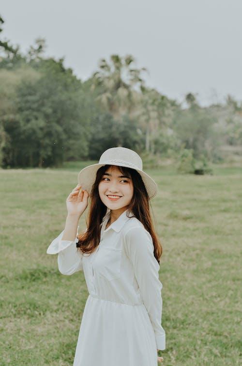 Femme En Chemise à Manches Longues Blanche Portant Un Chapeau Blanc Debout Sur Le Terrain De L'herbe Verte