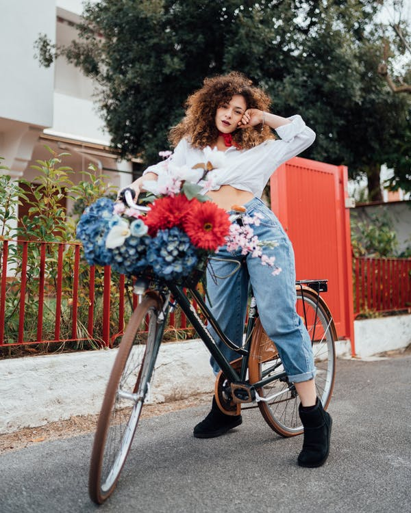 Woman in White Long Sleeve Shirt and Blue Denim Jeans Standing With  Bicycle on Road