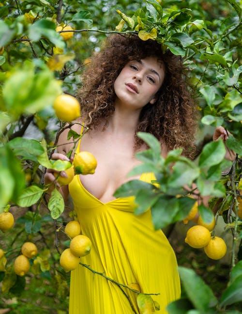 Woman  Dress Standing Beside Lemon Plants