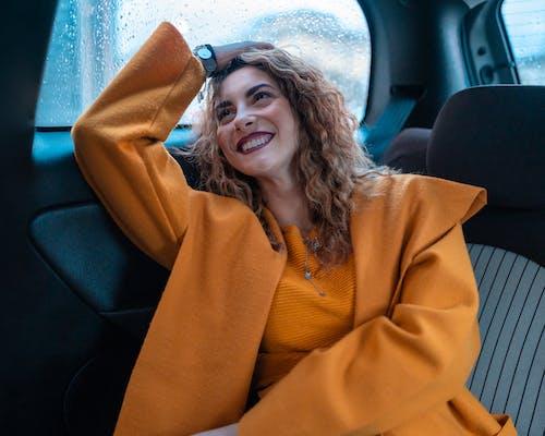 Woman in Orange Coat Sitting on Blue Car Seat
