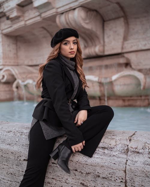 Woman in Black Coat and Black Pants Sitting on Concrete Near Water Fountain