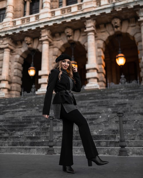 Woman In Black Coat And Black Pants Standing Near Stairs
