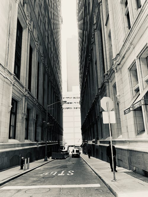 Black And White Photo Of Road In Between Buildings