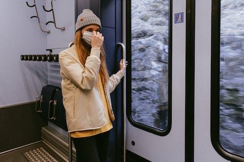 Woman in Beige Coat and Black Pants Standing Beside Glass Window