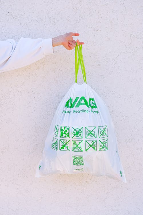 Person Holding White and Green Plastic Bag