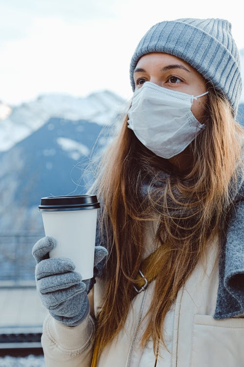 Woman Wearing Face Mask Holding White Disposable Cup