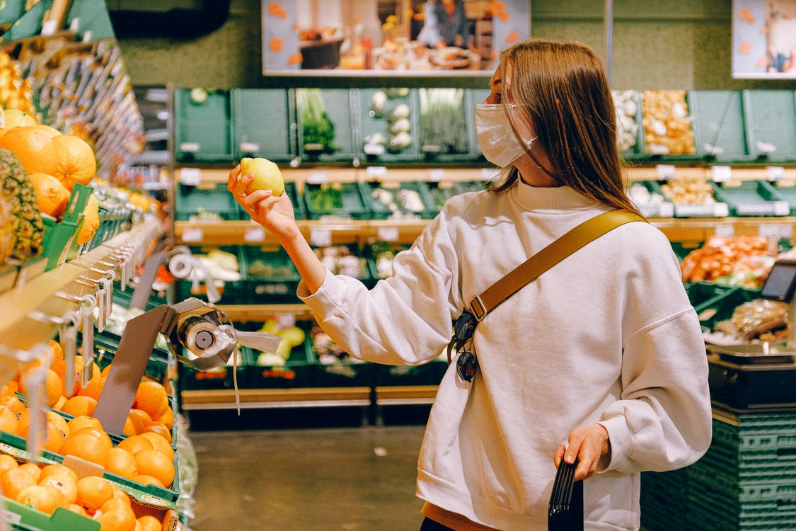 Woman in White Long Sleeve Shirt Holding Lemon Fruit