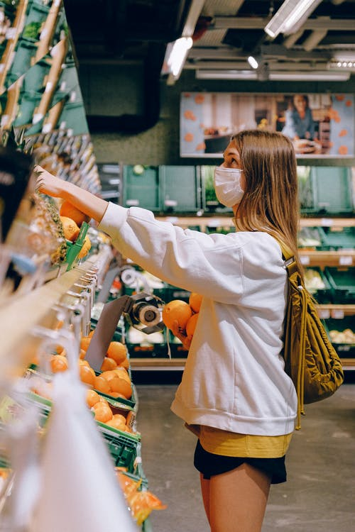 Woman in White Long Sleeve Jacket Shopping For Fruits