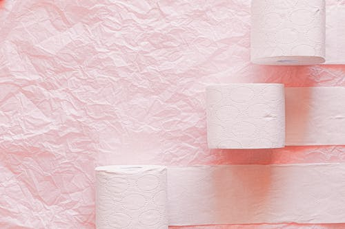 White Toilet Paper Roll on Pink Textile