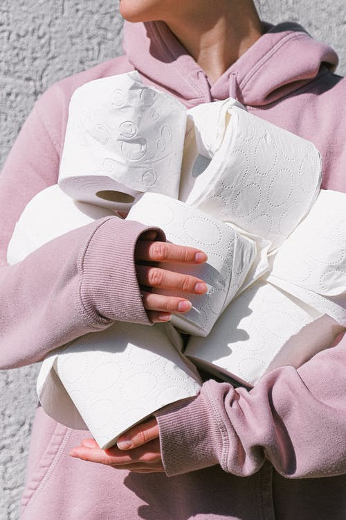 Person In Pink Long Sleeve Shirt Holding Tissue Rolls