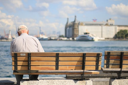 Man In Dress Shirt Sitting On Brown Wooden Bench Near Body Of Water