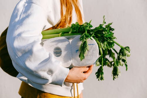 Person Carrying Tissue Rolls And Vegetables