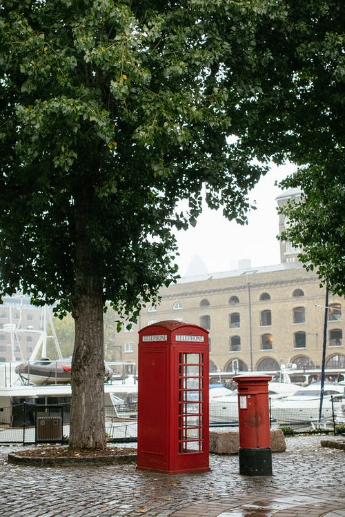 Red Telephone Booth Near Green Trees