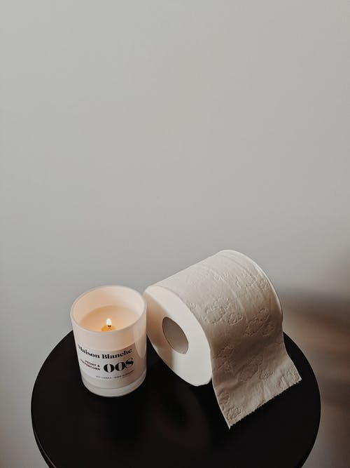 White Tissue Roll and Candle on Black Table