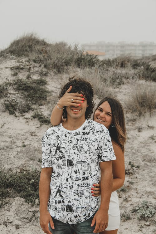 Woman in White and Black Floral Shirt Covering Man's Face With Her Hand