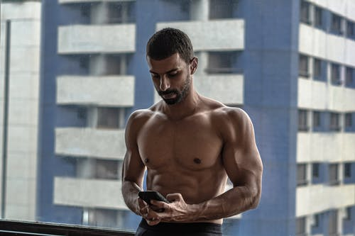 Topless Man Holding Black Smartphone