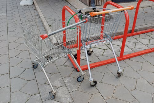 Shopping trolleys attached to metal stand near supermarket on street