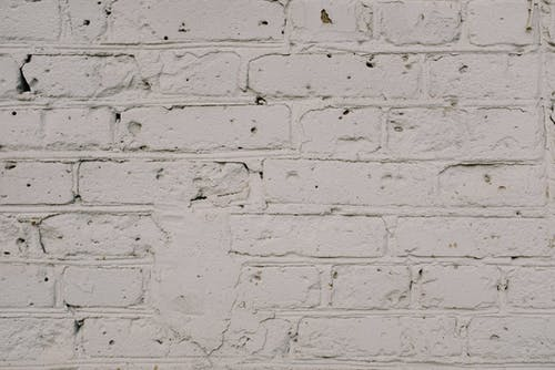 Old shabby brick wall with white paint