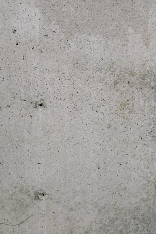Old shabby concrete wall with small holes