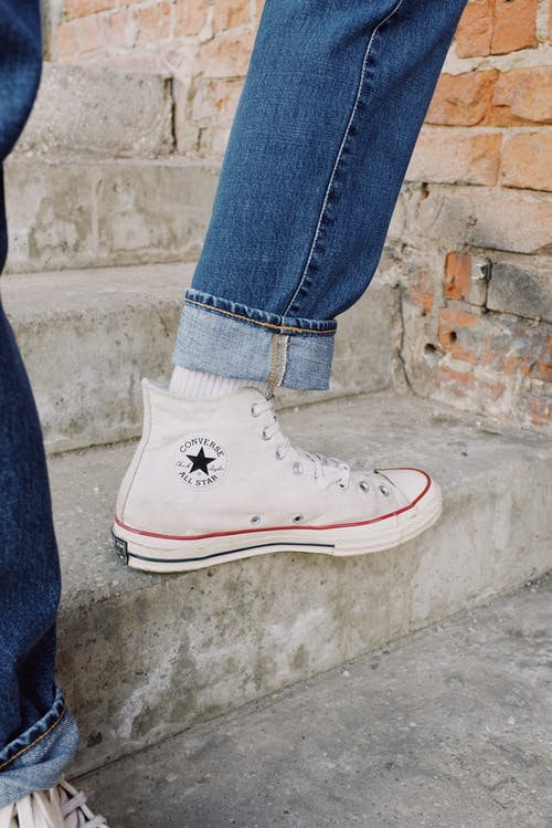 Person in Blue Denim Jeans Wearing White Converse All Star High Top Sneakers