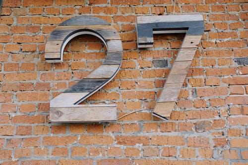 Big wooden number sign hanging on brick wall of modern building