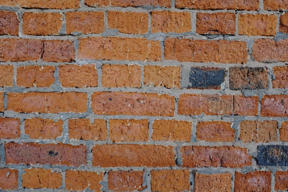Background of abstract old shabby brick wall of building on sunny street in city