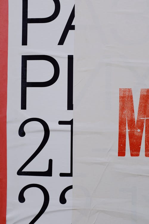 Letters and numbers printed on white banner placed on wall of modern building on street in city