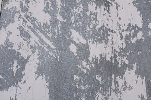 Old shabby metal surface with white paint on wall of old building