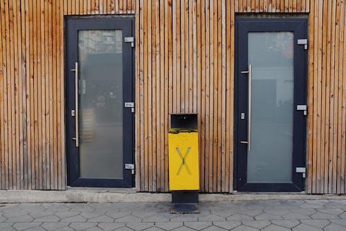 Metal trash bin placed near wooden wall between doors of building