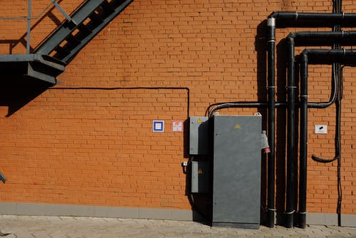Facade of modern building with metal staircase and transformer box near black metal tubes placed at brick wall