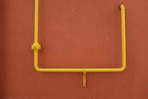 Yellow metal pipe on red wall