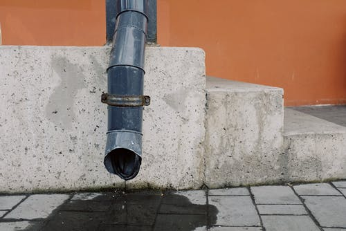 Metal drainpipe near concrete stairs of modern building on street