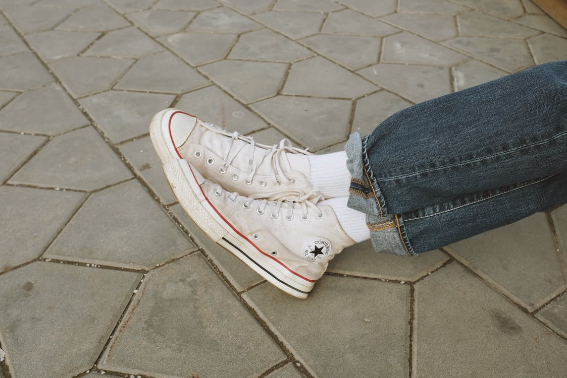 Person in Blue Denim Jeans and White Converse Sneakers